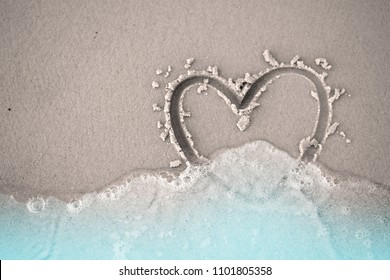 fading hand write draw heart shape on sand beach with blue water and sea foam bubble with copy space love lonely broken heart divorce concept