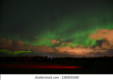 Fading northern lights behind orange clouds above Oulu in autumn