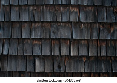 Fading wooden shingles on an old mill building.