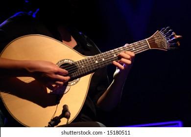 """fado"" - performer playing a tradicional portuguese guitar"
