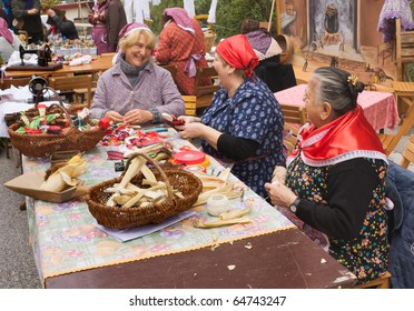 "FAENZA, ITALY - NOVEMBER 7: unidentified women make puppets with corn leaves at ""Fiera di San Rocco"" on November 7, 2010 in Faenza, RA, Italy. Re-enactment with old traditional clothing of rural life"