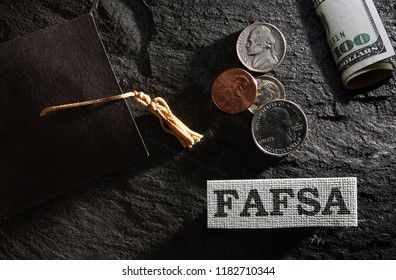 FAFSA (Free Application for Federal Student Aid) text with graduation cap and money -- financial aid concept