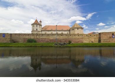 FAGARAS,BRASOV, ROMANIA - CIRCA JULY, 2015: Old castle mirrored by surrounding moat, Transylvania, Romania