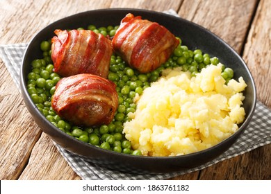 Faggots meatballs with a garnish of green peas and mashed potatoes close-up in a plate on the table. horizontal