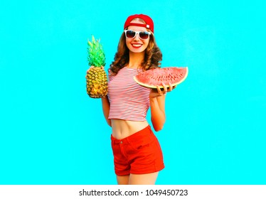 Fahion pretty slim smiling woman is holding a pineapple and a slice of watermelon over a colorful blue background wearing a red baseball cap