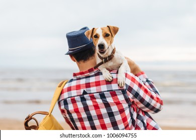 Fahionable male host of beauitiful dog, carries it on hands, come to see at sunset on seashore, spend time together, have good relationships. Unrecognizable man in checkered shirt with his pet