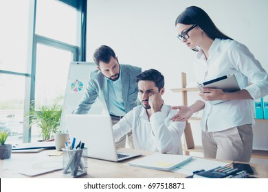 Fail, dissapointment, frustration concept. Three colleagues entrepreneurs are very upset seeing bad news at the laptop`s screen, all are wearing formal wear, lady is in glasses