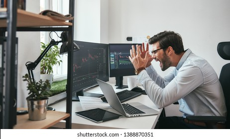 Failing! Frustrated young businessman or trader in formalwear is shouting and feeling angry while looking at trading charts and financial data in the office.