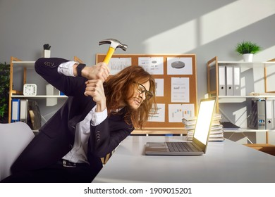 Failure, Internet spam, stress at work concept. Funny angry young office worker smashing mock up computer screen with hammer. Mad aggressive crazy guy annoyed with pop up ads breaks down laptop device