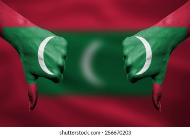 failure of Maldives - hands gesturing thumbs down in front of flag