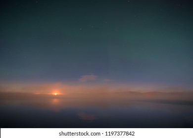 Faint northern lights above the lake, wild fire in background