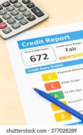 Fair credit score report with pen and calculator