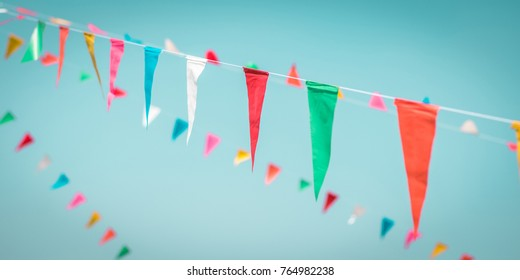 Fair flag blur bunting background hanging on blue sky for fun festa party event, summer holiday farm feast celebration, carnival festival event, park or street fiesta design decoration element