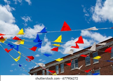 Fair flags blowing in the wind with blue skies and brick building in background.