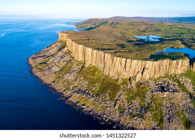 Fair Head big cliff and headland at the north-eastern corner of County Antrim, Northern Ireland, UK. Aerial view in sunset light with Atlantic Ocean and lakes. Far view of Torr Head in the background