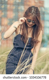 Fair skin young lady in tight fitting blue dress and curly long brown hairs stroll and look down. Hand clasping sunglasses with freight containers at the background.