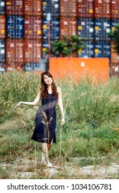 Fair skin young lady in tight fitting blue dress and curly long brown hairs stroll near freight containers at the background.