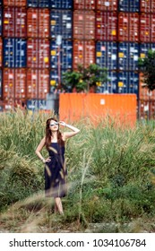 Fair skin young lady in tight fitting blue dress and curly long brown hairs wear sunglasses with hand on waist look upwards near freight containers at the background.
