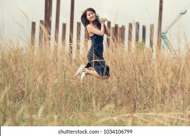 Fair skin young lady in tight fitting blue dress and curly long brown hairs jump both hands clasping sunglasses.