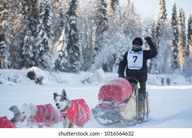 FAIRBANKS, ALASKA - FEBRUARY 3, 2018: Race veteran Matt Hall from Two Rivers, AK, waves to fans as he passes on the Chena River.