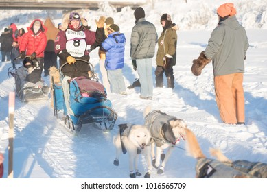 FAIRBANKS, ALASKA - FEBRUARY 3, 2018: Race veteran Ryne Olson, from Two Rivers, AK, waives to race fans as she heads down the trail.