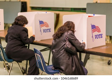 FAIRFAX COUNTY, VIRGINIA, USA - NOVEMBER 4, 2008: Women voters at polls during presidential election, paper ballots.