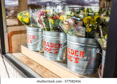 Fairfax, USA - January 18, 2017: Buckets of flowers with Trader Joe's signs viewed from outside of store