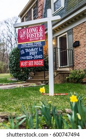 Fairfax, USA - March 7, 2017: Long and Foster real estate sign in front of townhouse with yellow daffodils