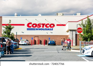 Fairfax, USA - September 8, 2017: People with shopping carts filled with groceries walking out of Costco store in Virginia in parking car lot