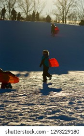 Fairfax, Virginia - January 14, 2019: A girl carries her sled after sliding down a hill while others at the top of it await their turn to do the same at Van Dyke Park in the City of Fairfax.