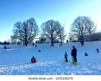 Fairfax, Virginia - January 14, 2019: Families enjoy an afternoon of sledding at Van Dyke Park in the City of Fairfax following a snowstorm that dropped a foot of snow in the Northern Virginia area.