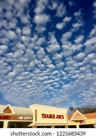 Fairfax, Virginia - November 8, 2018: Late afternoon sunlight bathes a Trader Joe's grocery store under a unique, cloudy blue sky.