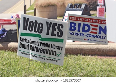 """Fairfax, Virginia, United States - September 19, 2020: A """"Vote Yes"""" sign for a Library Bond Referendum sits next to a Biden campaign sign at the Fairfax County Government Center during early voting."""