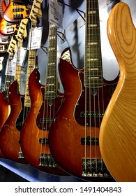 Fairfax, Virginia / USA - August 29, 2019: A variety of electric bass guitars for sale hang on a wall at a Guitar Center store.