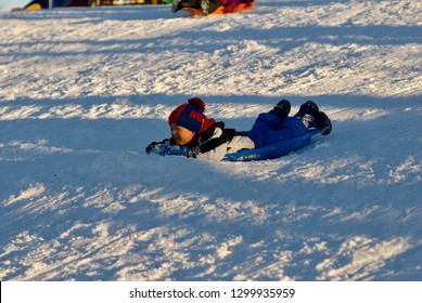 FAIRFAX, Virginia, USA - January 14, 2019: A boy sleds down a hill at Van Dyke Park in the City of Fairfax following a winter storm that dumped nearly a foot of snow in Northern Virginia.
