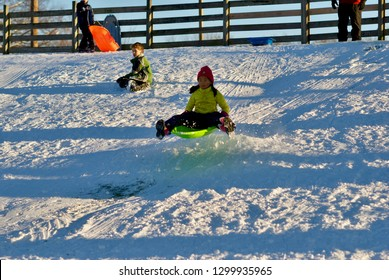 FAIRFAX, Virginia, USA - January 14, 2019: A girl and boy sled down a hill at Van Dyke Park in the City of Fairfax following a winter storm that dumped nearly a foot of snow in Northern Virginia.