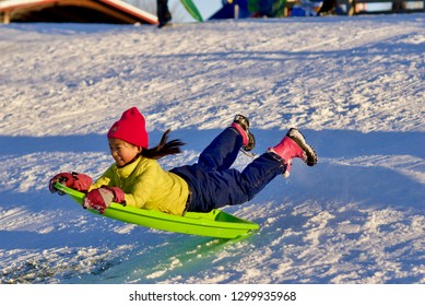 FAIRFAX, Virginia, USA - January 14, 2019: A girl flies down a sledding hill at Van Dyke Park in the City of Fairfax following a winter storm that dumped nearly a foot of snow in Northern Virginia.