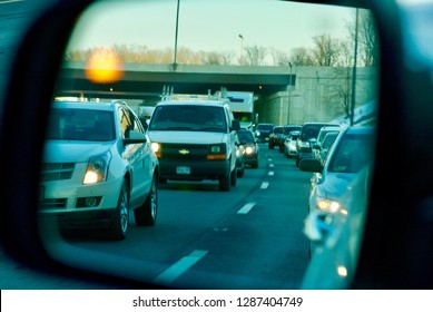 """Fairfax, Virginia, USA - January 15, 2019: Heavy traffic during afternoon rush hour on I-495, """"The Capital Beltway"""", is seen in a rearward-looking side mirror showing a yellow blindspot warning light."""