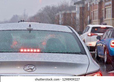 Fairfax, Virginia, USA - January 29, 2019: Commuters wait at a stoplight in the City of Fairfax Historic District as  snow begins to fall from Winter Storm Jayden as it blankets Northern Virginia.