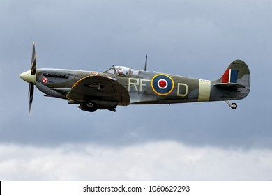 Fairford, Gloucestershire, UK - June 19, 2011: A Supermarine Spitfire Mk Vb, AB910, flying in a cloudy sky