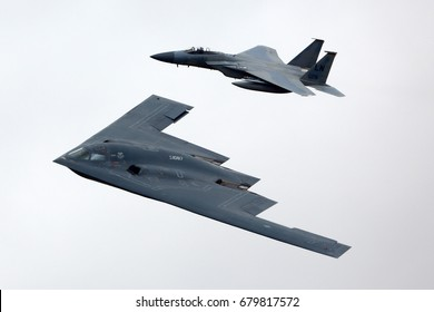 FAIRFORD, UNITED KINGDOM - JULY 16, 2017: Northrop B-2A Spirit and McDonnell Douglas F-15C Eagle of US air force in formation during demo flight at Royal International Air Tattoo show at Fairford AFB