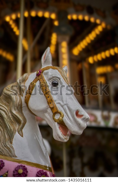 Fairground carousel with horse's head in forground