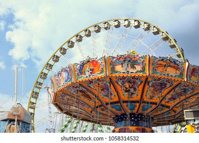 Fairground with chain carousel and ferris wheel
