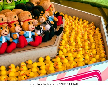 Fairground duck-hook game; close-up of rubber ducks floating in fairground booth; close up;