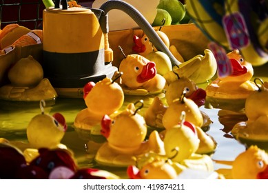Fairground duck-hook game; close-up of rubber ducks floating in fairground booth; close up; differential focus