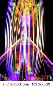 Fairground lights spinning at night long exposure