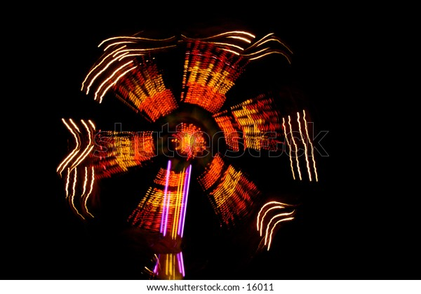Fairground ride at night showing motion blur lights.