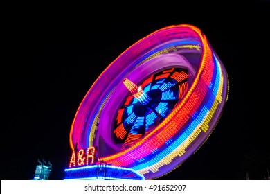 Fairground ride spinning in a blur of colour
