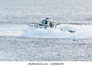Fairhaven, Massachusetts, USA - August 31, 2018: Fairhaven harbormaster patrol boat smashing through wake of high-speed ferry while responding to a call for assistance