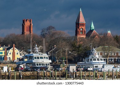 Fairhaven, Massachusetts, USA - January 30, 2019: Towers of Congregational Church (l) and Fairhaven Town Hall (r) loom over marina on Acushnet River